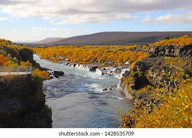 A scenic view of the Hraunfossar waterfalls, located near Husafell and Reykholt in West Iceland. A viewpoint with amazing view over the Hraunfossar and Hvita River.
