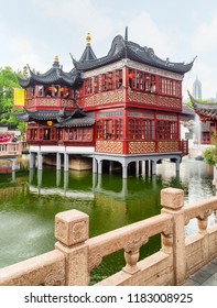 Scenic view of Hu Xin Ting Teahouse (Mid Lake Pavillion) at Yuyuan Garden in the Old City of Shanghai in China. Beautiful traditional red wooden Chinese building on stilts.