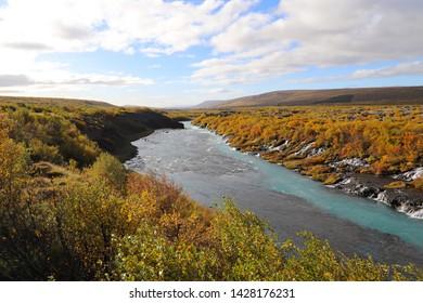 Scenic view of Hvita River and Hraunfossar waterfalls. Hraunfossar is a series of waterfalls runs out of the Hallmundarhrau lava field into the Hvita river.
