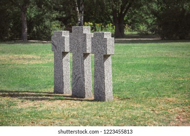 scenic view of identical old gravestones on grass at graveyard