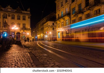 A scenic view of the illuminated Market Square and Belfry in the evening in the foreground b and the lights of passing trams, Lviv, Ukraine. Night winter landscape.