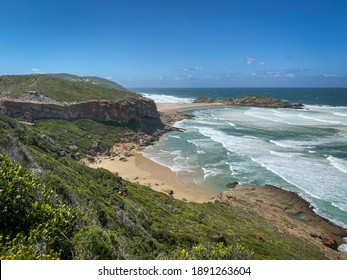 Scenic view of Indian Ocean and coastline with beaches at Robberg Nature Reserve, Plettenberg Bay, South Africa against blue sky