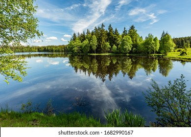 Scenic view of a Kladska lake in the Czech Republic, close to Marianske Lazne surrounded with forest. Sunny summer landscape with blue sky and white clouds and reflection in water. - Shutterstock ID 1682990167