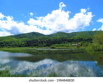 Scenic view of lake Cerknica and Javorniki hills in Notranjska, Slovenia with a reflection of the hills and the clouds in the lake - Shutterstock ID 1984848830