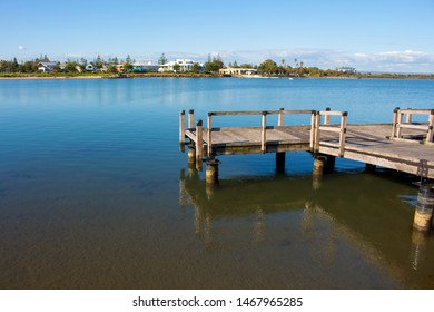 Scenic view of the little wooden Pump jetty on an ebbing tide reflected in the calm  Leschenault Estuary at Bunbury Western Australia on a afternoon in late winter which is used as a fishing platform.