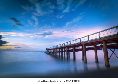 Scenic view of long wooden pier on shoreline with colorful sunset and cloudscape background, Reunion Island.