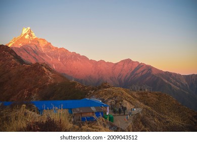 Scenic view of Machhapuchre himal and small lodge situated at the base; trekking route of Mardi himal; summer season; early morning; red mountain and hills; visitors enjoying the pleasant view.