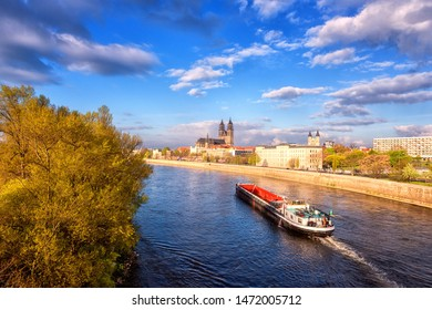 Scenic view of Magdeburg with cathedral, river Elbe and cargo boat, beautiful bright morning cityscape with blue sky and clouds, Saxony, Germany. Outdoor travel background