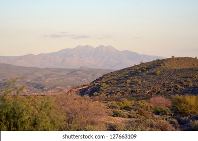 A scenic view of the magnificent desert surrounded by mountain peaks, at McDowell Mountain Regional Park in Arizona, at twilight.