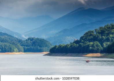 Scenic view of majectic mountain lake Vidraru with travel boat. in Carpathian mountains at Romania, wild nature landscape in the summer, panoramic view. Dramatic picturesque scene. Beautiful world.