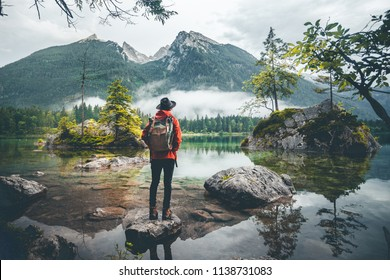 Scenic view of a man wearing a red jacket, a hat and a backpack looking at mountains, Lake Hintersee, Berchtesgaden, Germany