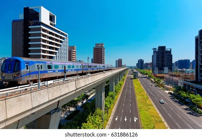Scenic view of a metro train traveling on elevated rails of Taoyuan Mass Rapid Transit System (Taoyuan International Airport MRT System) under sunny blue sky in Chunli, New Taipei City, Taiwan