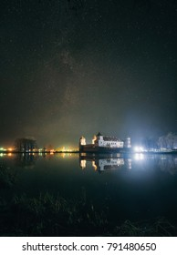 Scenic view of Mir Castle Complex at night with starry sky and glow reflexion on lake. Landmark in Belarus