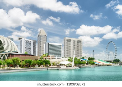 Scenic view of modern buildings and Marina Bay with azure water in Singapore. Beautiful sunny summer cityscape. Singapore is a popular tourist destination of Asia.