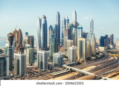 Scenic view of modern city architecture. Aerial daytime skyline of Dubai Marina, UAE, with skyscrapers and highways. Summer travel background.