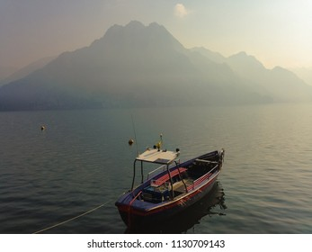 Scenic view. Moored lonely small fishing boat ship in calm lake or serene sea water early in the morning on misty mountains scenery harbor nature landscape background. Italy, Lombardia, Riva di Solto