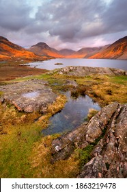 Scenic view of mountains and lake at sunset with golden light and moody clouds. Wastwater, Lake District, UK. - Shutterstock ID 1863219478