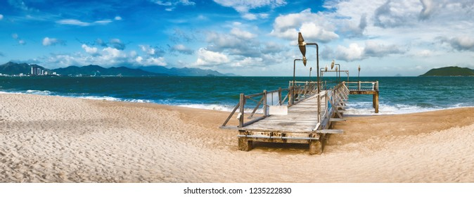 Scenic view of Nha Trang beach at sunny day. Beautiful tropical landscape. Pier on the foreground. Panorama