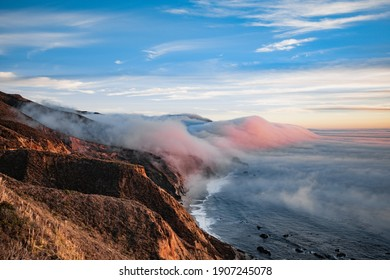 Scenic view of ocean shore near Big Sur, California, USA. Cloud covered coast, sea and cliff hills. Foggy pink sunset landscape.