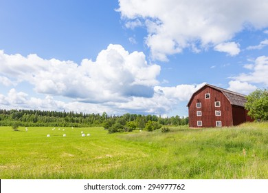 Scenic View of an Old Barn with White Silage Balls with a Blue Sky