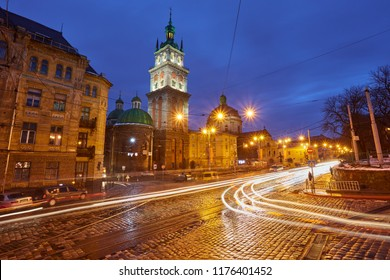 Scenic view on illuminated Assumption Church Bell Tower at twilight with vintage tram on foreground, Lviv, Ukraine. Night winter scenery.