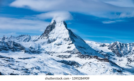 Scenic view on snowy Matterhorn peak in sunny day with blue sky and some clouds in background, Switzerland