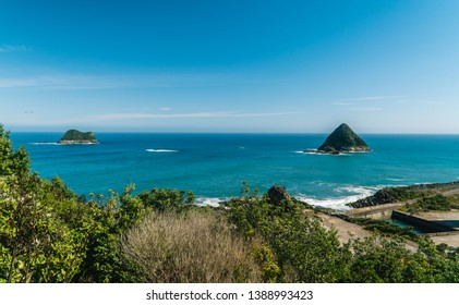 Scenic View out to an island, off coastal walkway, at Paritutu Rock. Blue, scenery, sea, landscape, exotic concepts. Green foreground frame. Shot in New Plymouth, North island, New Zealand, NZ.
