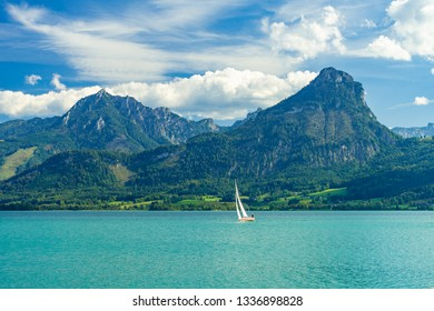 Scenic view over Wolfgangsee with a lonely sailing boat and the Northern Limestone Alps
