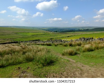 scenic view of a path on the edge of moorland in calderdale west yorkshire with rough tussock grass with dry stone walls bordering pastureland with farmhouses and pennine hills visible in the distance