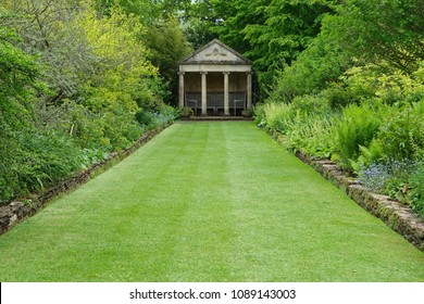 Scenic View of a Peaceful Garden with a Freshly Mowed Lawn and Flower Bed in Bloom