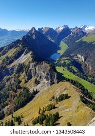 "scenic view from the peak of a Swiss mountain with the lake ""Saemtisersee"" down in the valley"