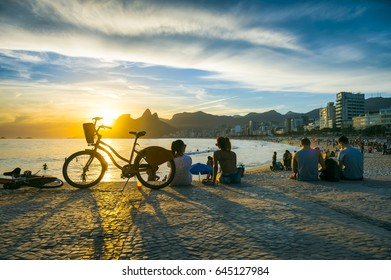 Scenic view of people and bicycle at sunset in Rio de Janeiro, Brazil from the Arpoador end of Ipanema Beach