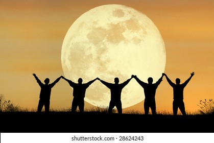 A scenic view of people raising their hands with the full moon in the background
