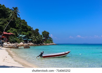 Scenic view of Perhentian Kecil island bah with a boat in blue sea and buildings in the jungle