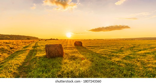 Scenic view at picturesque burning sunset in a green shiny field with hay stacks, bright cloudy sky , trees and golden sun rays, summer valley landscape