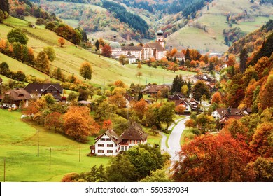 Scenic view of a picturesque mountain valley in autumn. Colourful countryside landscape with mountain forests, traditional houses and old monastery. Germany, Black Forest. Colorful travel background.