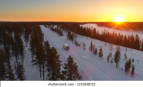 Scenic view of pine forest landscape and speeding van on snowy freeway at sunset