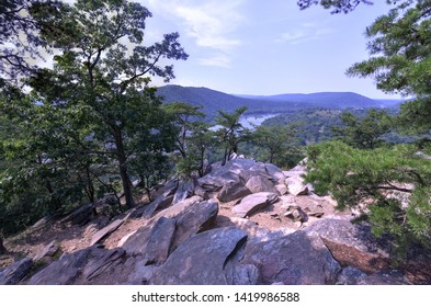 Scenic view of the Potomac River and across to Short Hill Mountain from Weverton Cliffs on the Appalachian Trail. A rocky outcrop points to the river below, surrounded by evergreens on a summer day.