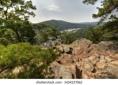 Scenic view of the Potomac River & Short Hill Mountain from Weverton Cliffs on the Appalachian Trail in Maryland. A rocky cliff points to the river below, surrounded by trees on a bright, summer day.