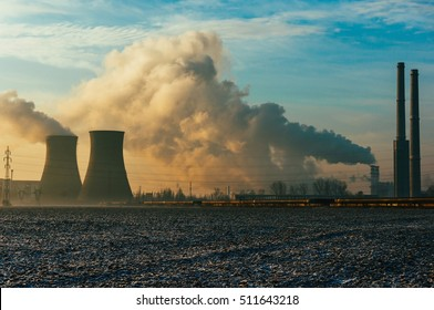 Scenic view of power refinery chimneys billowing smoke at sunset.