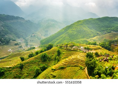 Scenic view of rays of sunlight illuminating green rice terraces through storm clouds at highlands of Sapa District, Lao Cai Province, Vietnam. Sa Pa is a popular tourist destination of Asia.