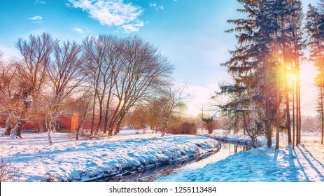 Scenic view of the river and trees covered by snow. Sunset time