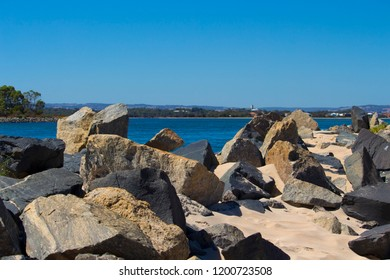 Scenic  view of  the rocky groyne from the sandy beach  at the Cut  where Leschenault Estuary enters the Indian ocean  near Australind Western Australia on an early  morning in autumn.