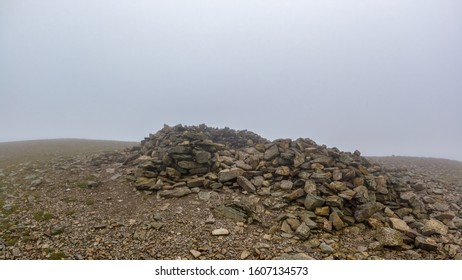 A scenic view of a rocky mountain summit with a stony cairn under a misty sky