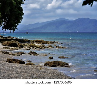 Scenic view of a rocky shoreline with the Davao Oriental mountains in the background, southern Philippines.