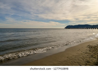 Scenic view of the sandy beach of Alassio with the pier and the cape of Capo Mele on the horizon, Alassio, Liguria, Italy