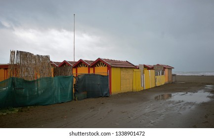Scenic view of the sandy beach of Versilia,  with colorful wooden hut,  on a grey winter day
