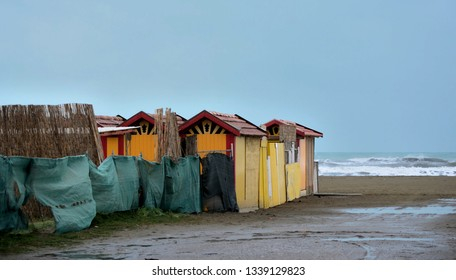 Scenic view of the sandy beach of Versilia, with colorful wooden huts, on a grey winter day
