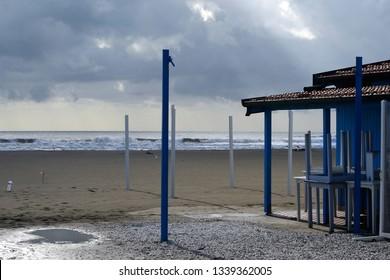 scenic view of sandy beach of Versilia coastline with its wooden huts, on winter season