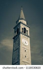 Scenic view of Santa Maria Assunta bell tower against blue sky. Remanzacco. Udine, Friuli Venezia Giulia. Italy Vintage preset.